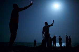 World Press Photo of the Year 2013 John Stanmeyer, USA, VII for National Geographic 26 February 2013, Djibouti City, Djibouti African migrants on the shore of Djibouti city at night, raising their phones in an attempt to capture an inexpensive signal from neighboring Somalia—a tenuous link to relatives abroad. Djibouti is a common stop-off point for migrants in transit from such countries as Somalia, Ethiopia and Eritrea, seeking a better life in Europe and the Middle East.