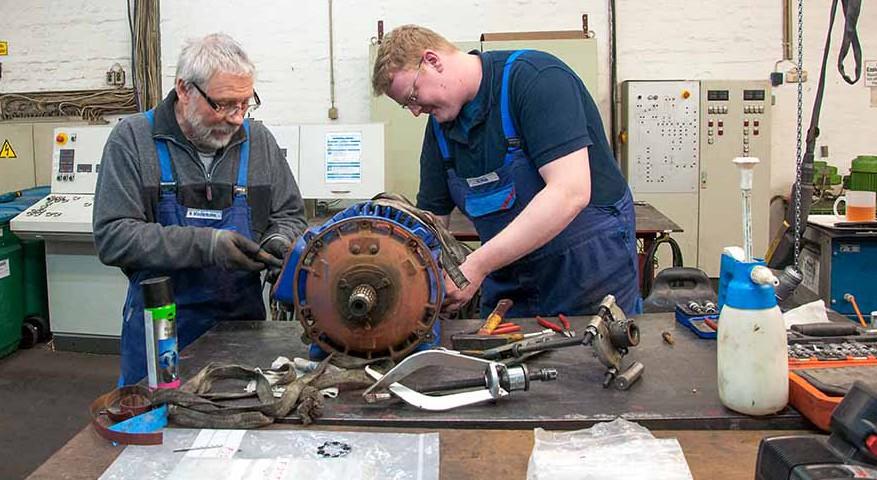 Wolfgang Wiedemann (li.) und Boris Pick bauen den Motor von der Magnetanlage eines Krans auseinander. Foto: Nadine Albach