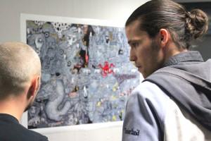 Rechts der Künstler Pablo Barajas Stollmeier vor einem seiner ausgestellten Werke im Gespräch mit einem Gast.