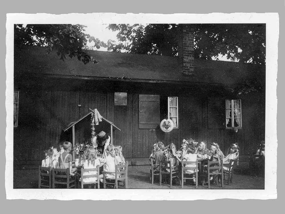 Mittagessen vor den Baracken auf dem Nordmarkt. Bei trockenem Wetter wurde draußen auch gegessen, spätestens aber danach mussten die Kinder nach draussen. Drinnen machten die Betreuerinnen die Betten für den strikt überwachten Mittagsschlaf.