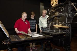 Besucher in der Ausstellung an einer Handdruckpresse aus dem 19. Jahrhundert.Foto: Technoseum