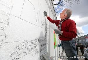 """Mauer Galerie, Streetart 2015 in der Weißenburger Straße am Kraftwerk. Peter Krüger aus Gütersloh skizziert seine Arbeit """"Großstadtgetriebe"""""""