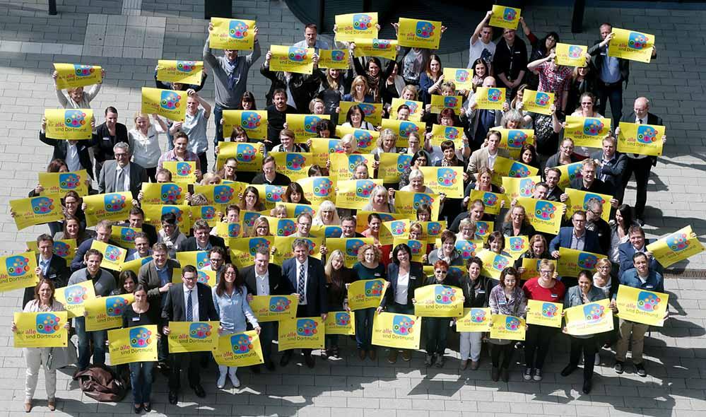 """Im Anschluss an die Personalversammlung stellten sich die Mitarbeiter der BIG mit den Kampagnenplakaten """"Wir ALLE sind Dortmund"""" auf. Foto: BIG/Stephan Schütze"""
