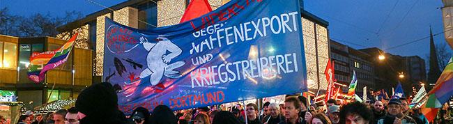 Demo gegen Bundeswehreinsatz in Syrien führt durch ein Spalier von  Glühweintrinkern