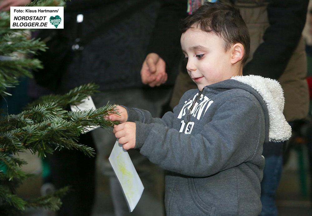 Interkultureller Weihnachtsmarkt im Schleswiger Viertel. Der kleine Fabian hängt seinen Wunsch zum Fest an den Baum