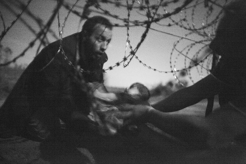 Ein Foto des australischen Fotografen Warren Richardson hat den World Press Photo Wettbewerb 2015 gewonnen. Das Foto zeigt einen Mann, der an der ungarisch-serbischen Grenze in Röszke ein Baby durch den Grenzzaun reicht.