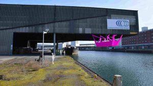 Die Kunstfahrten in einer pinkfarbenen Stahlskulptur sollen das Publikum unter die Überdachung einer Werkhalle heben.