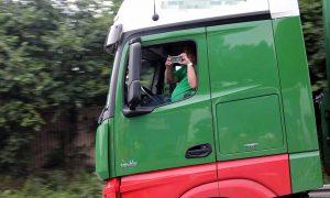 Das Handy am Steuer - auch beidhändig filmt dieser LKW-Fahrer - bei voller Fahrt auf der Autobahn.