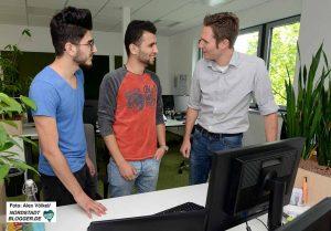 Tim Elberich, Abteilungsleiter für das Projekt- und Systemgeschäft, im Gespräch mit zwei seiner Azubis.