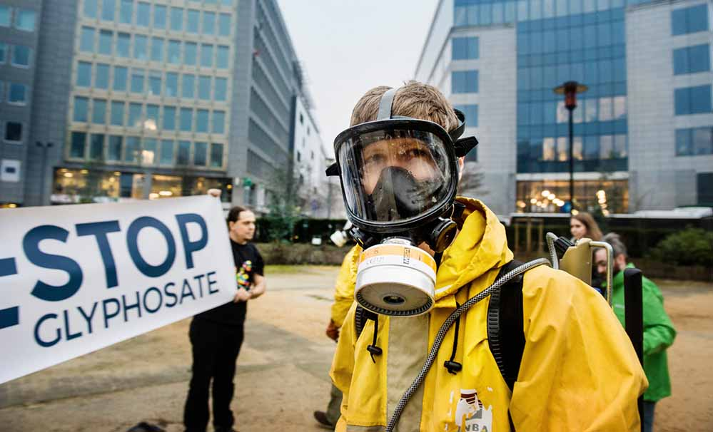 "Foto: Eric De Mildt/ Greenpeace activists, wearing protective clothing and masks, display a banner outside the European Commission that reads ""Stop Glyphosate."" Greenpeace and other environmental and health organisations are meeting in Brussels (as well as Madrid, Rome, Berlin and Paris) to launch a European Citizens' Initiative (ECI) to ban glyphosate, reform the EU pesticide approval process, and set mandatory targets to reduce pesticide use in the EU. The goal is to collect at least one million signatures from Europeans and submit the petition before the Commission's next move to renew, withdraw or extend the EU licence of glyphosate."