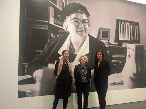 Die Kuratorinnen (v.li.) Caro Delsing, Regina Selter und Karoline Sieg vor einem großformatigen Porträt von Gründungsdirektorin Leonie Reygers.